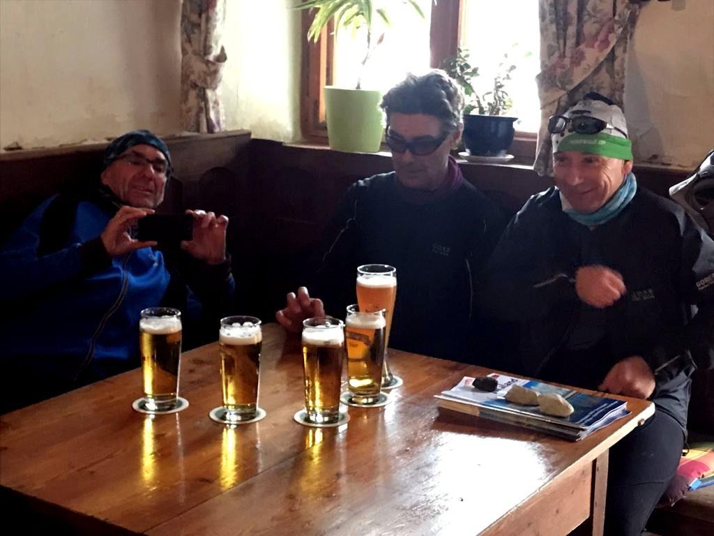 das Bier steht am Tisch, die drei Biker freuen sich
