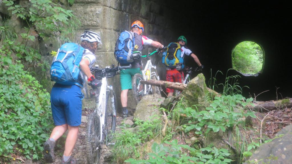 drei MTB´ler schieben die Räder in einen alten Bahntunnel
