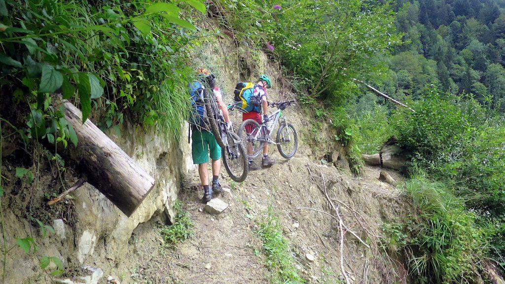 zwei Mountainbiker tragen ihre Räder an einer schmalen Passage -Transalp vom Bodensee zum Comer See