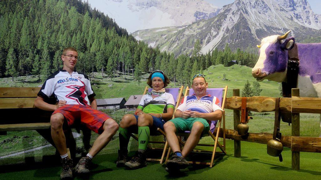 drei Biker vor einer Fototapete mit Bergen -Transalp vom Bodensee zum Comer See