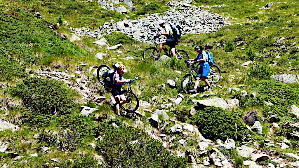 Biker tragen ihr Rad in unwegsamem Gelände -Transalp vom Bodensee zum Comer See