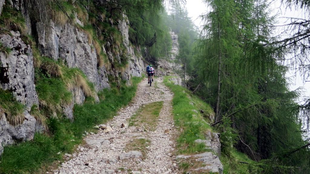 ein Mountainbiker fährt eine alte Militärstraße hoch. Links die Wand, rechts der Abgrund