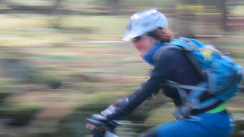 schnelle Bikerin fährt von rechts durch das Bild
