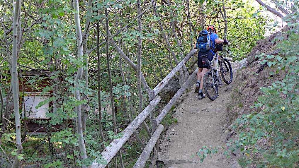 Ein Mountainbiker schiebt sein Rad einen Weg über dem Marteltal im Vinschgau hoch