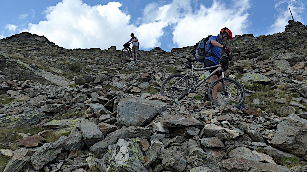 Biker tragen Ihre Räder vom Tarscher Pass herunter