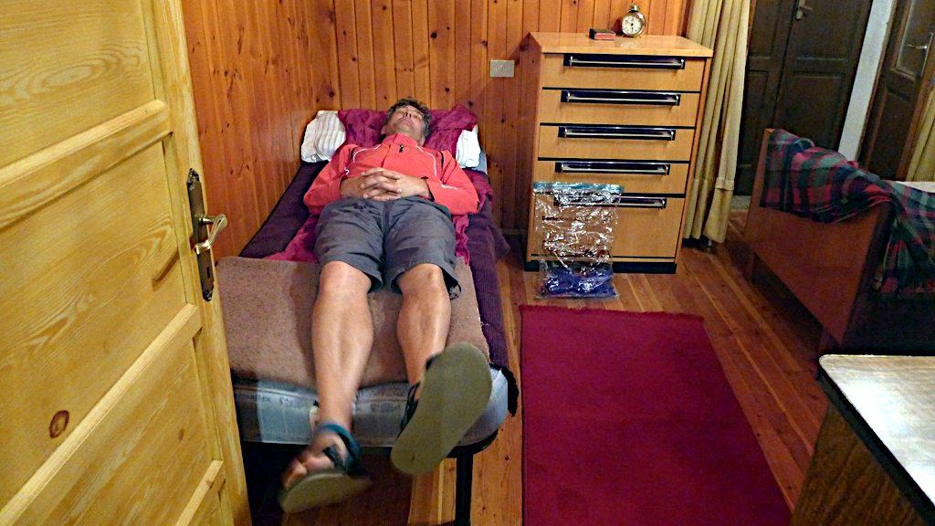 Ein Mann liegt auf viel zu kurzem Bett