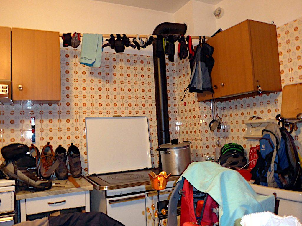 In einer Küche hängen viele Kleidungsstücke zum Trocknen