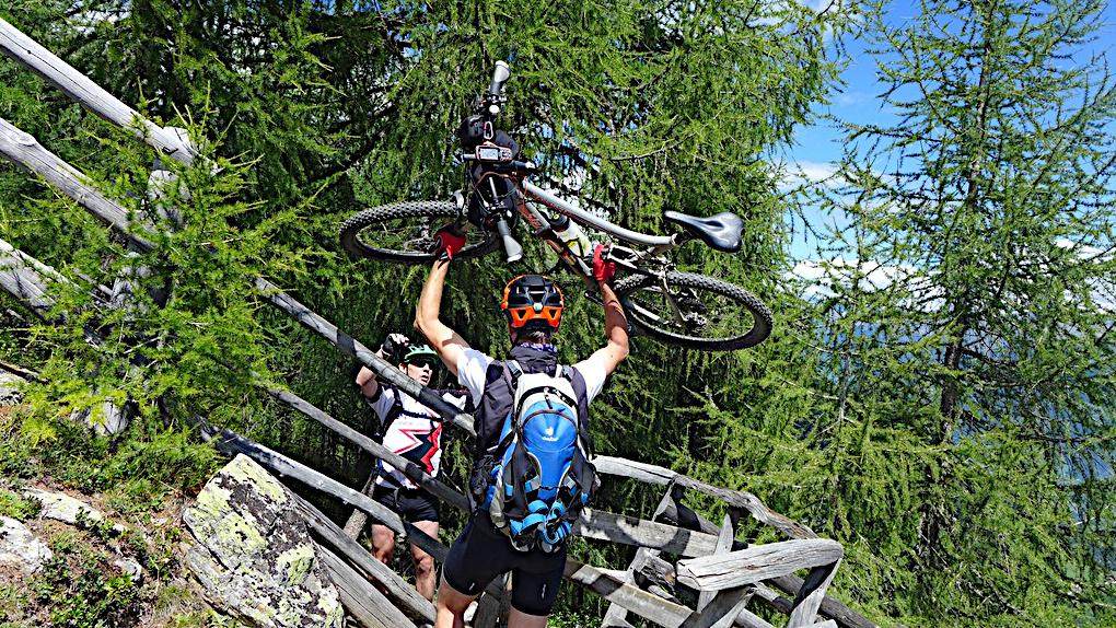Zwei Biker heben ein Rad über einen Weidezaun