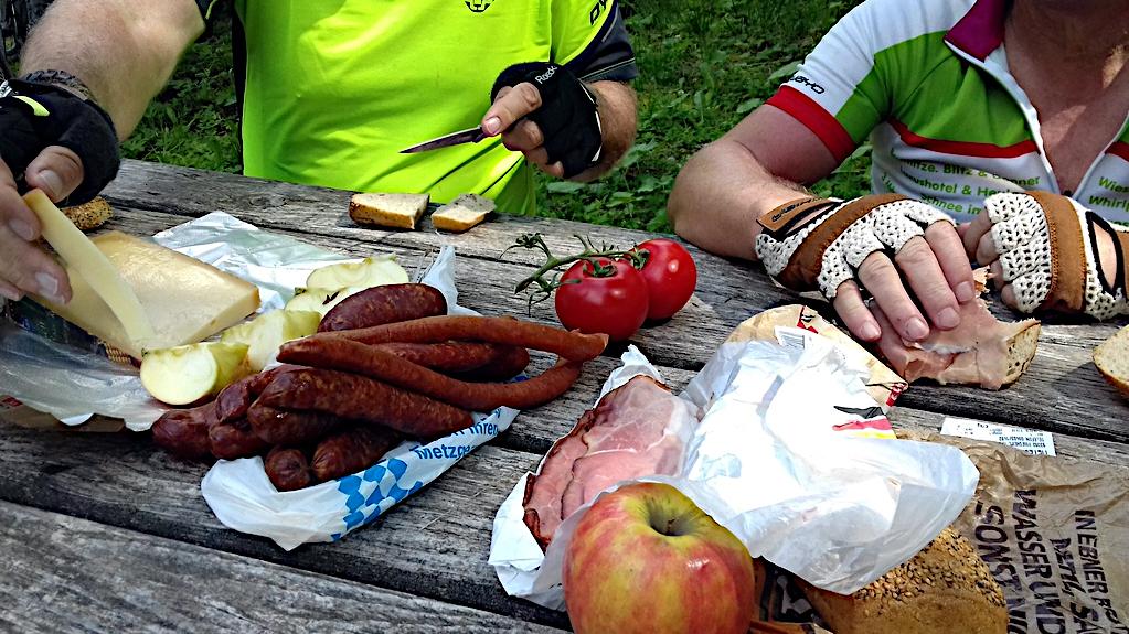 Auf einem rustikalten Tisch liegen viele Zutaten für eine deftige Brotzeit