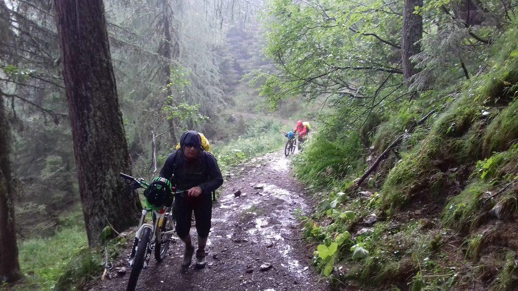 zwei Biker schieben im Regen ihre Räder hoch zum Passo Palombino