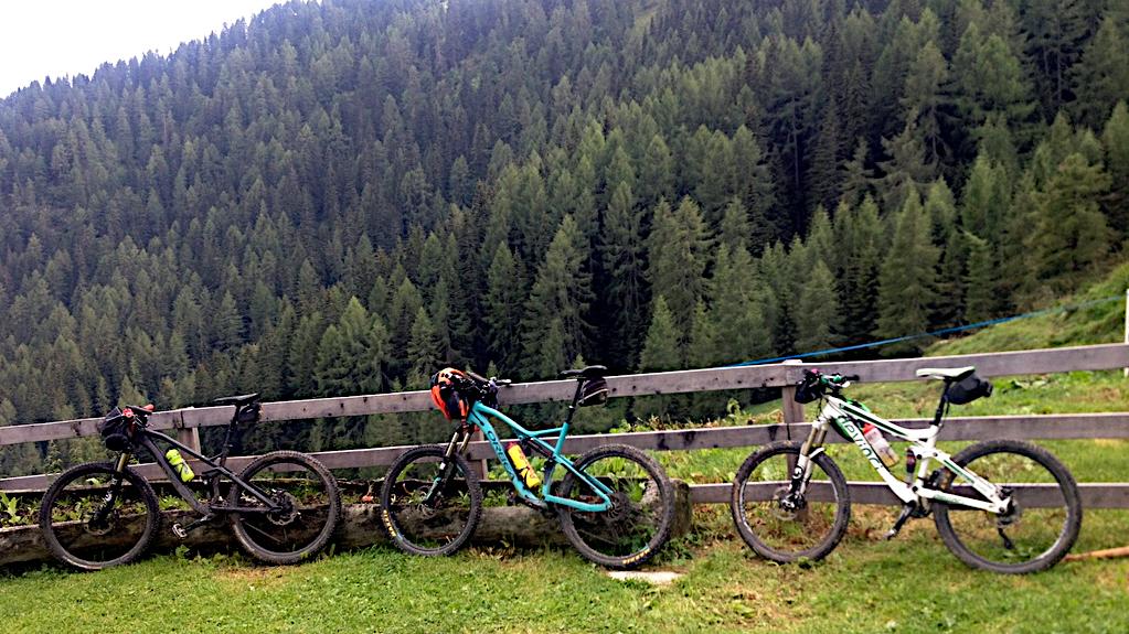 drei Mountainbikes stehen am Weidezaun der Malga Dignas