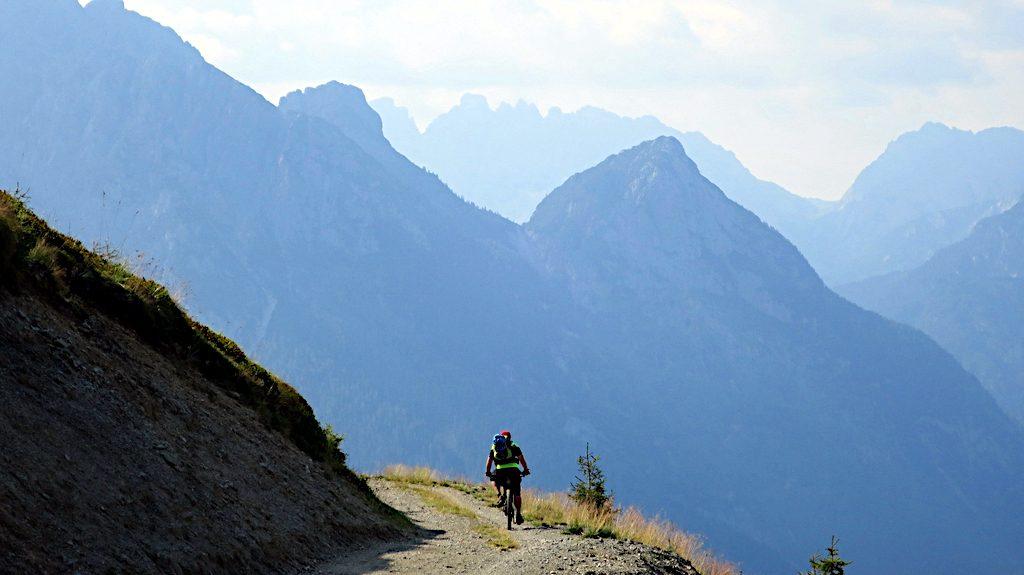 ein Mountainbiker fährt auf einer breiten Piste zum Passo Dignas. Im Hintergrund Berge der Karnischen Alpen