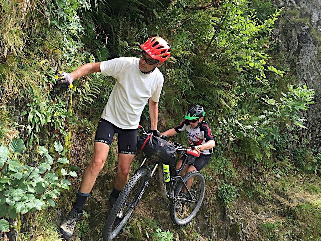 Zwei Biker überwinden ein fehlendes Stück der Via Alpina wie der Karnische Höhenweg hier auch heißt