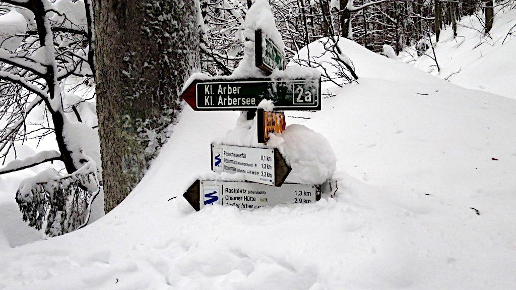Ein tief eingeschneiter Pfosten mit Wanderweg Markierungen