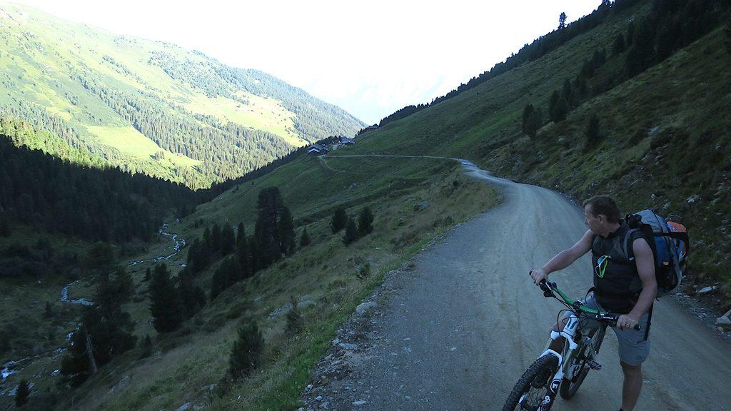Ein Mountainbiker ist auf dem Weg zum Geiseljoch. Er steht im Schatten während der Gegenhang schon in der Sonne liegt