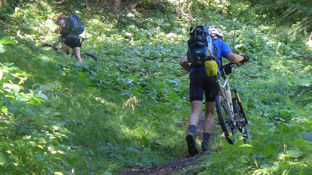Zwei Biker schieben die Räder über eine Wiese steil hoch