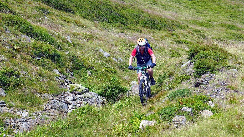 ein Mountainbiker für über einen steinigen Wiesenweg Richtung Gossensaß ab