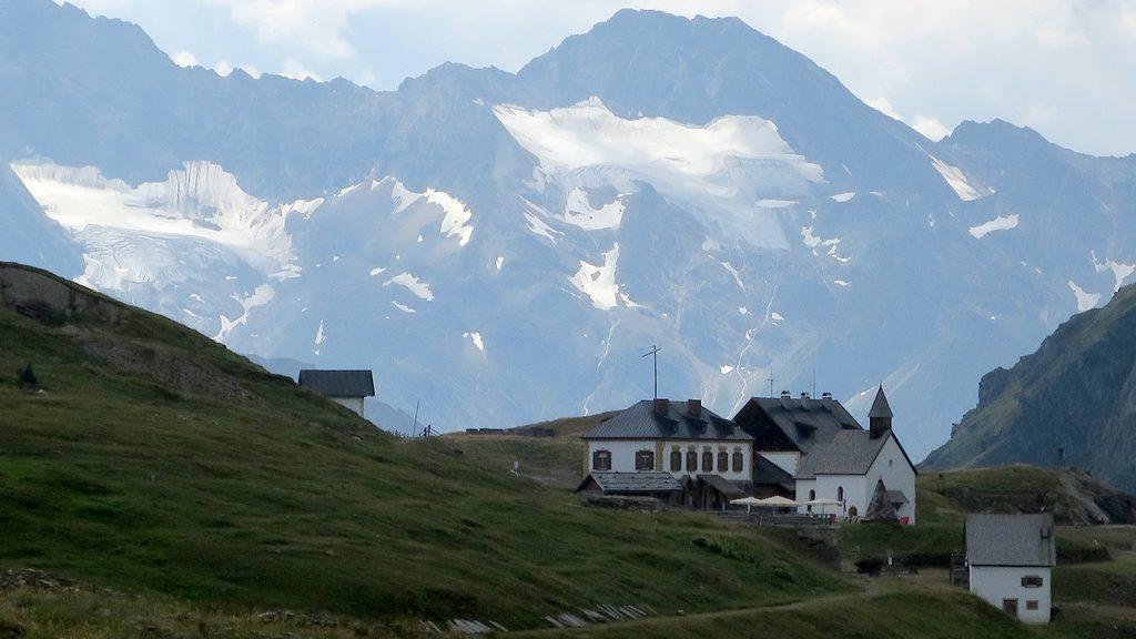 Die Gebäude St. Martin am Schneeberg und die Schneeberghütte vor Bergkulisse