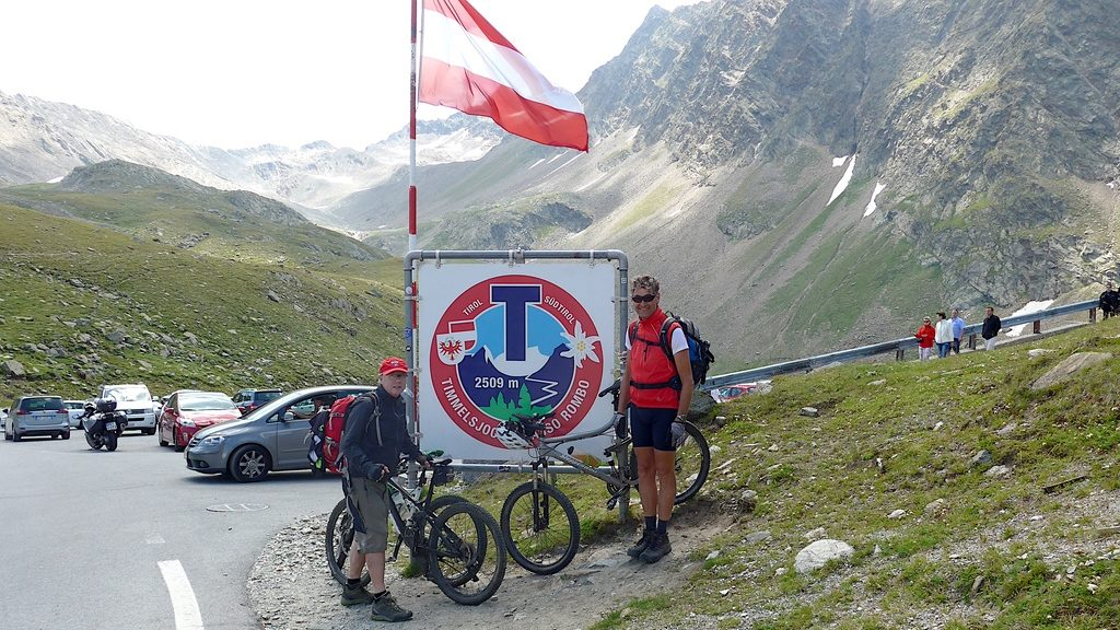 Zwei stolze Mountainbiker vor dem Pass-Schild Timmelsjoch 2509 m