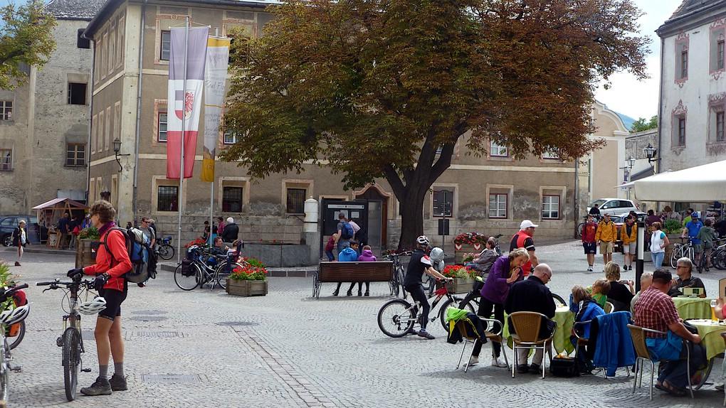 Ein Platz in Glurns. Radtouristen sitzen vor dem Cafe