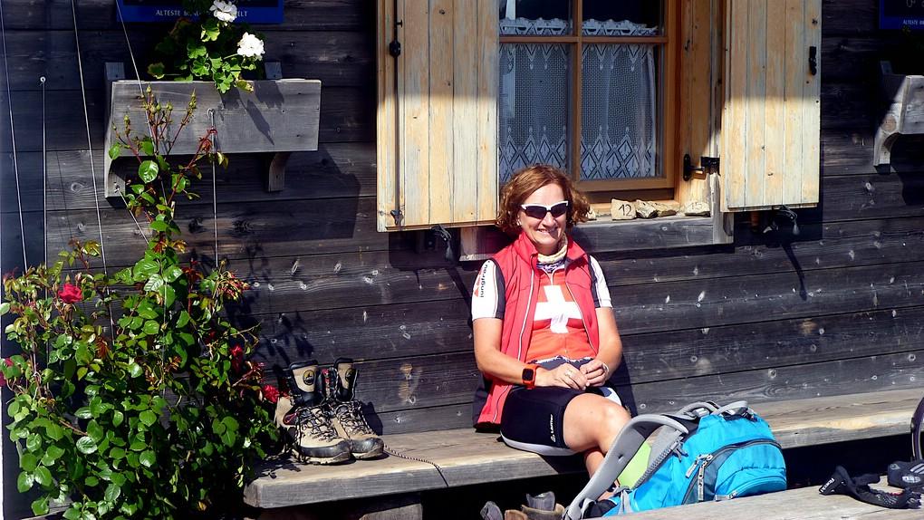 Eine Bikerin sitzt in der Sonne vor der Gamper Alm