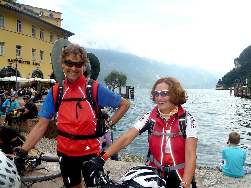 Zwei sehr zufriedene Biker sind nach ihrer Alpenüberquerung für Einsteiger am Hafen von Riva angekommen