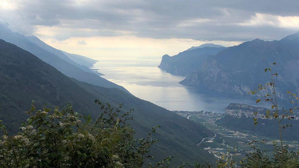Von hoch oben geht der Blick Richtung Süden. Man sieht den Gardasee zwischen seinen Bergen liegen. Im Vordergrund Torbole und der Brione.