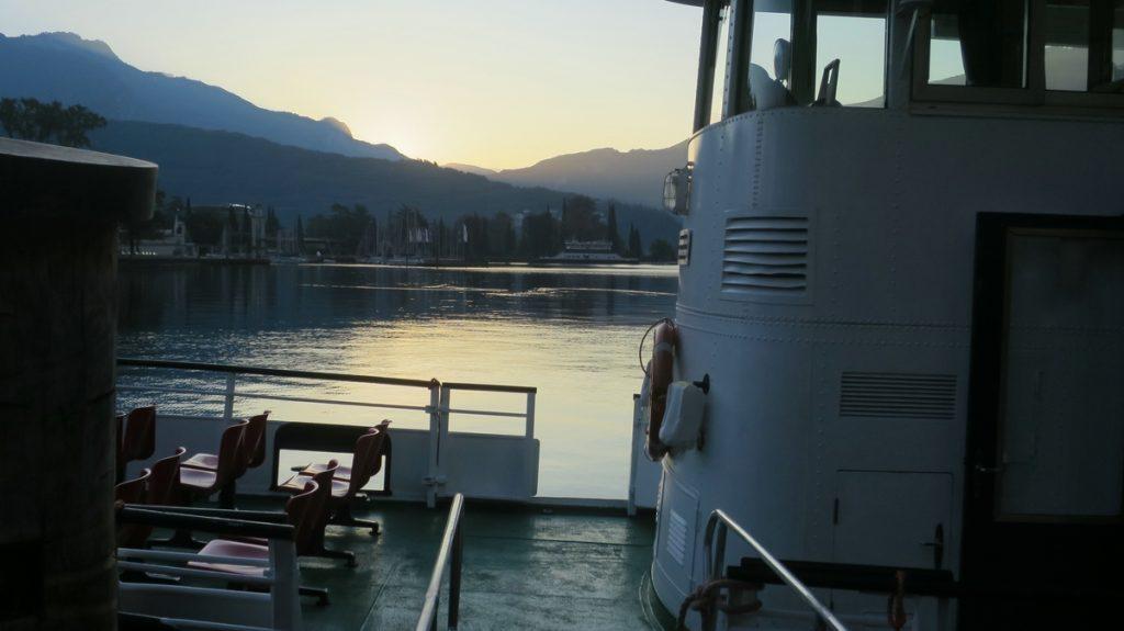 Es ist früher Morgen und der Gardasee liegt glatt. Im ersten Licht sieht man Teile des Schiffes welches uns zu eine Mountainbiketour nach Limone bringen wird.