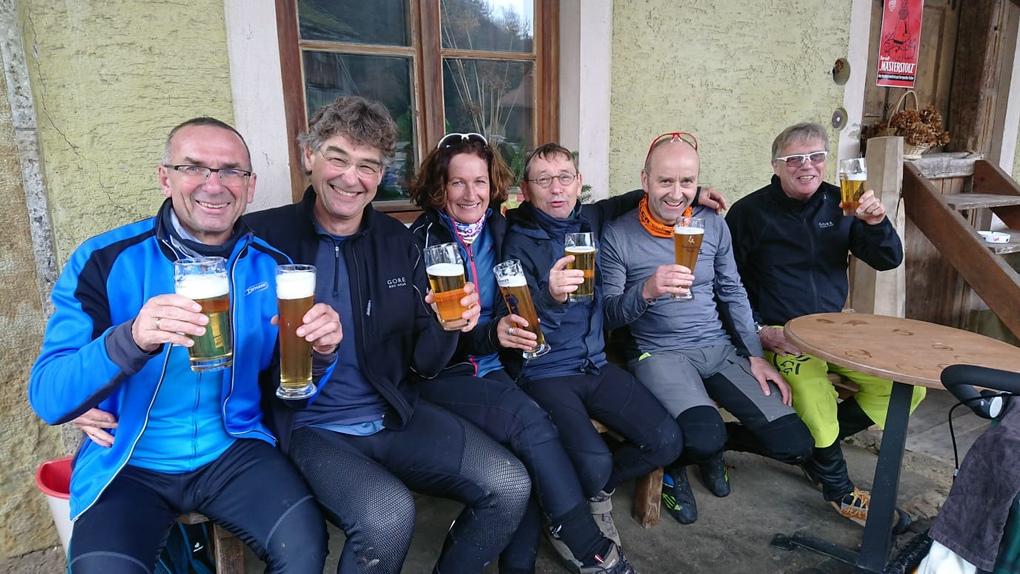 Sechs zufriedene Biker mit einem Bier in der Hand