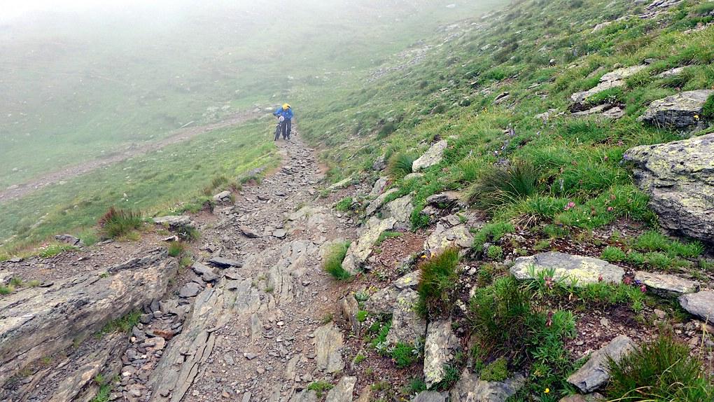 Mühsam schiebt ein Mountainbiker beim Schweizcross sein Rad zum Bistinepass hoch.
