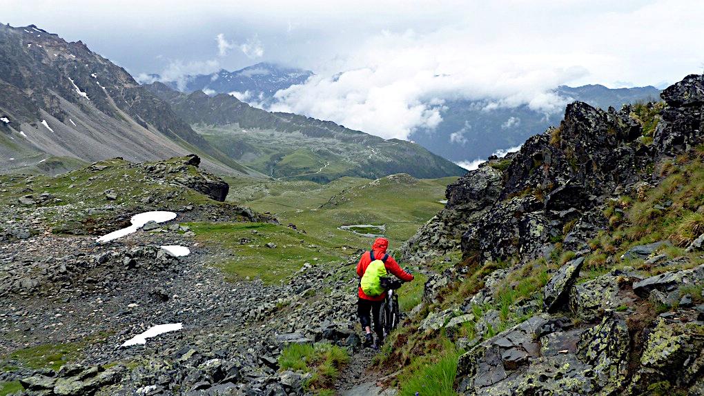 Ein Mountainbiker schiebt sein Rad am Meidpass
