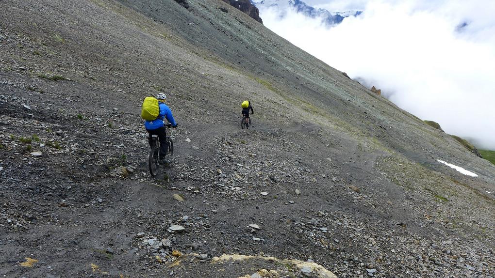 Zwei Mountainbiker fahren auf weichem Untergrund vom Pas de Lona ab.