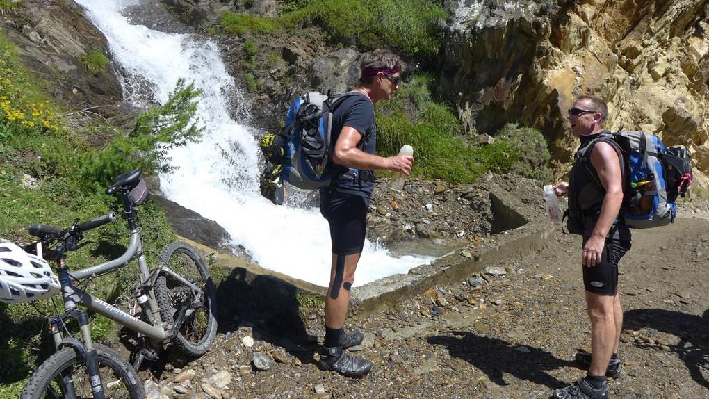 Zwei ältere Mountainbiker stehen an einem Gebirgsbach