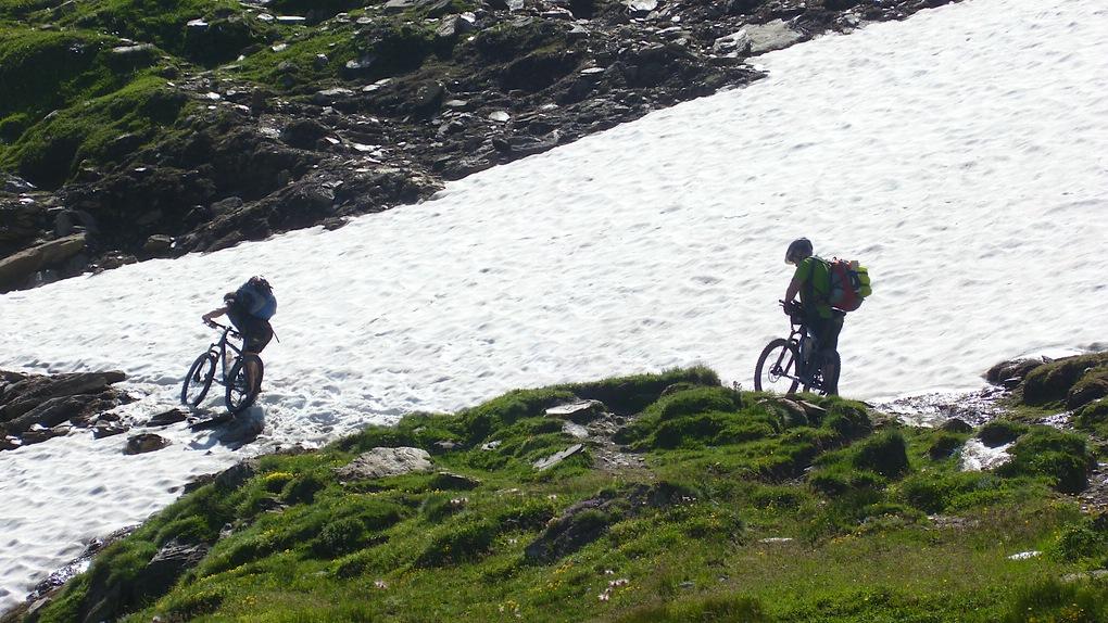 Zwei Mountainbiker an einem Altschneefeld