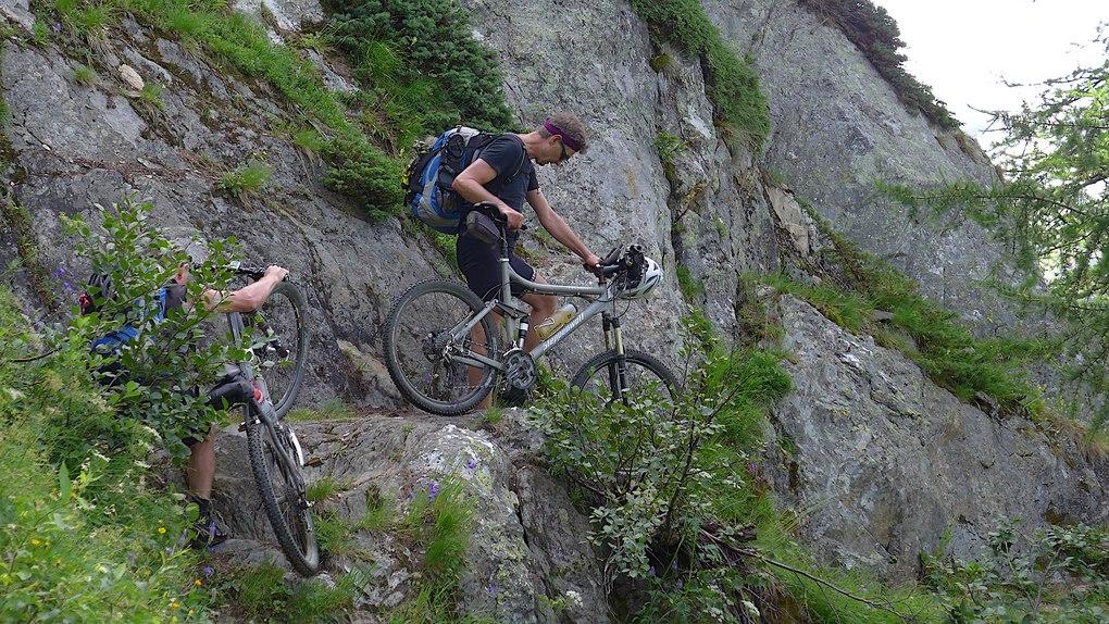 Mountainbiker schieben beim Schweizcross durch eine Felswand