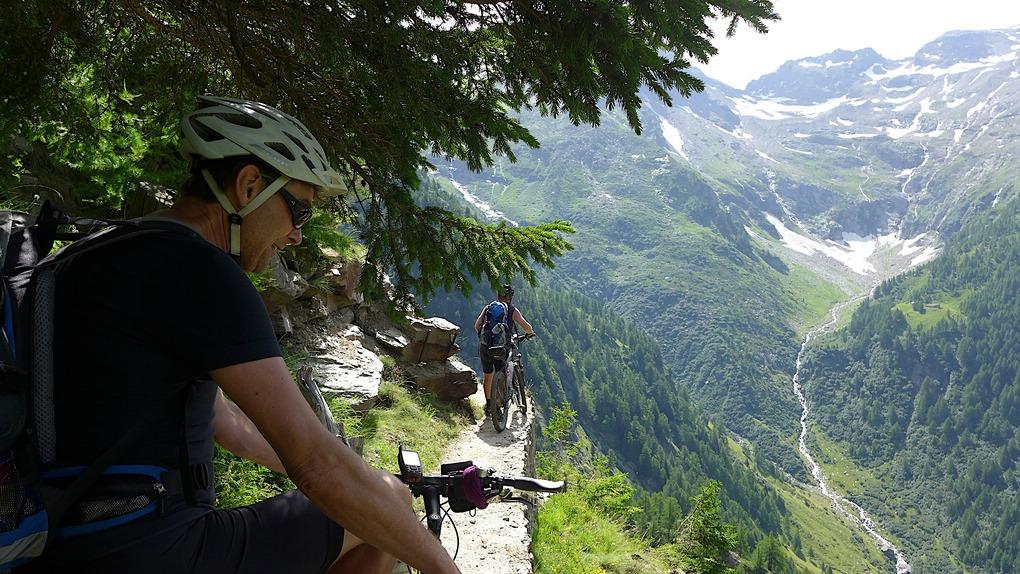 Zwei Biker auf einem schmalen Pfad hoch über einem Tal im Wallis