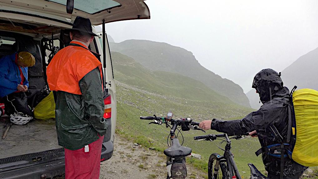 Drei Menschen am Berg in strömenden Regen.
