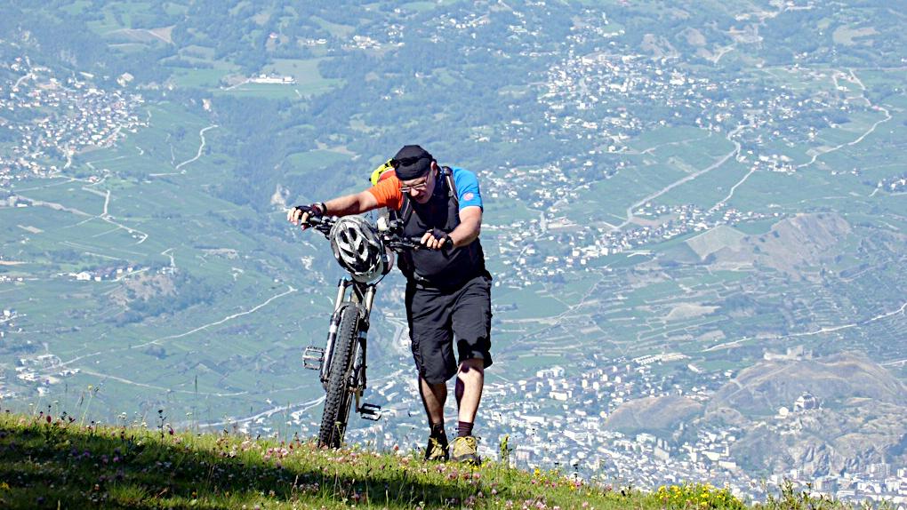 Ein Biker schiebt sein Rad sehr steil hoch. Weit unten im Tal sieht man Ortsschaften