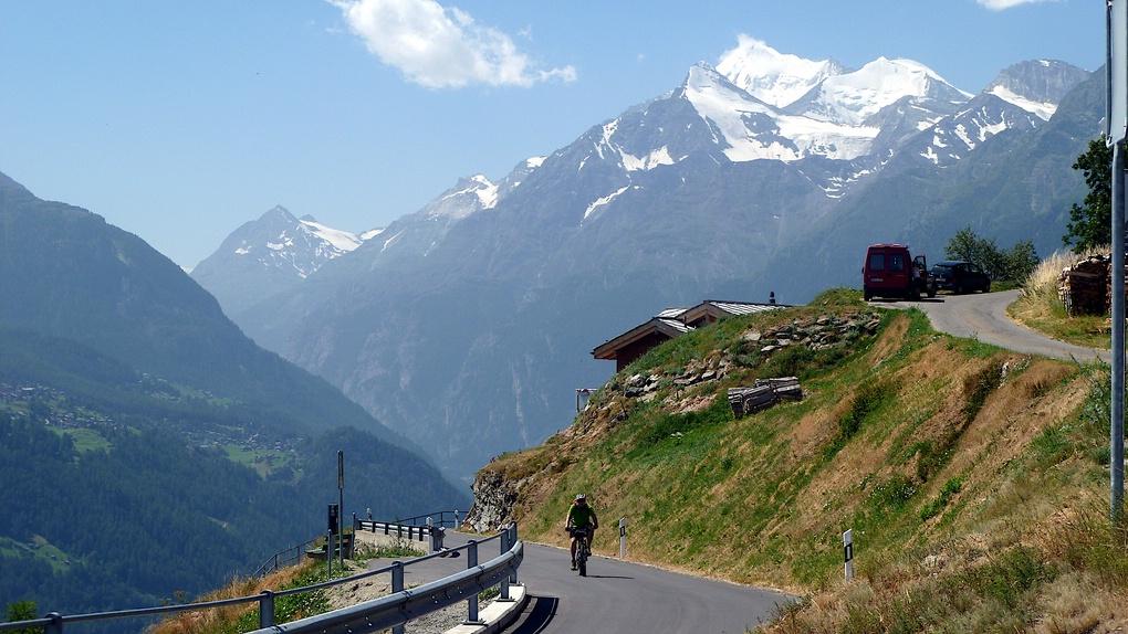 Mit den Walliser Bergen im Hintergrund fährt ein Mountainbiker eine Straße hoch