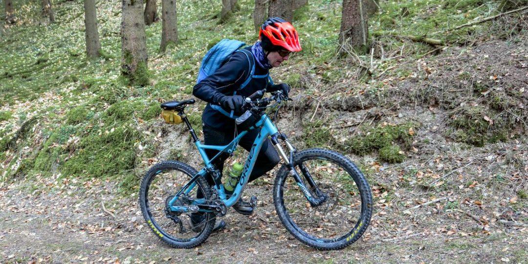 Ein Mountainbiker schiebt den Berg hoch